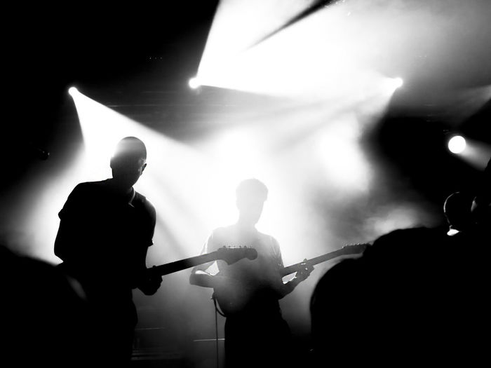 Silhouette people playing guitar at music concert