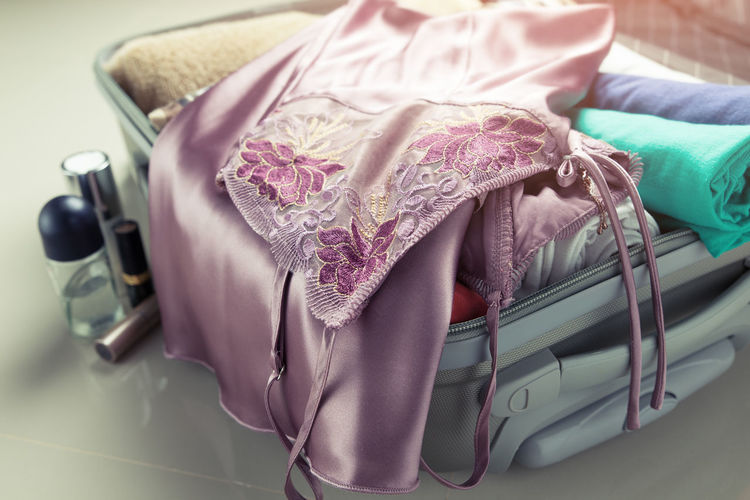 Packing clothes into travel bag Bag Baggage Bed Belonging Close-up Clothes Day Fashion Fold Honeymoon Indoors  Lace Luggage Nightdress Nightgown Nightwear No People Packing Purse Romantic Satin Silk Sleepwear Travel Wear