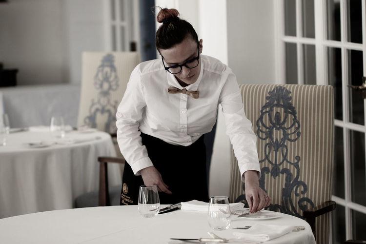 Waitress arranging place setting