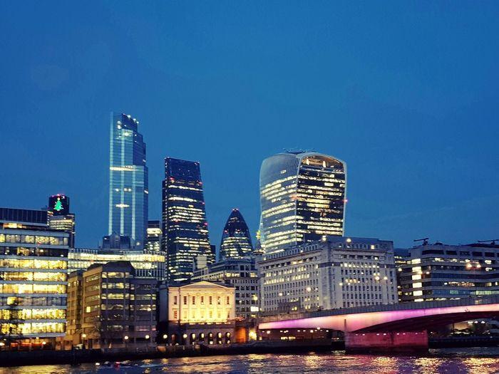 Illuminated buildings in city against blue sky at dusk
