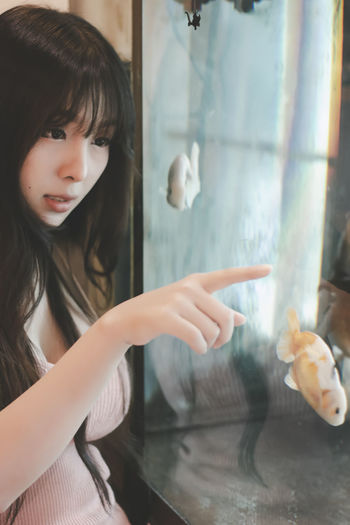 Girl looking at fish in glass