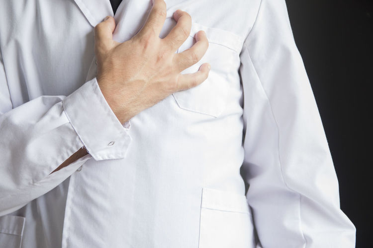 Midsection of doctor touching chest in pain