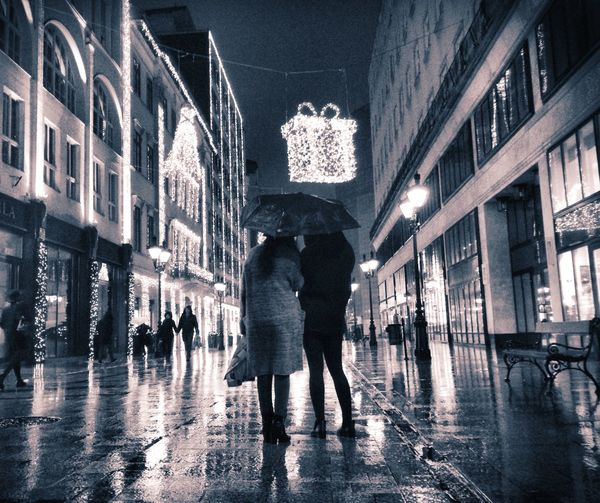 Rear View Of People With Umbrella Standing On City Street At Night During Christmas