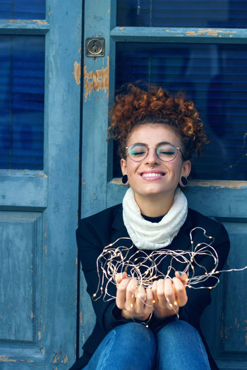 Beautiful Woman Building Exterior Casual Clothing Curly Hair Day Front View Happiness Leisure Activity Lifestyles Looking At Camera One Person Outdoors People Portrait Real People Sitting Smiling Young Adult Young Women