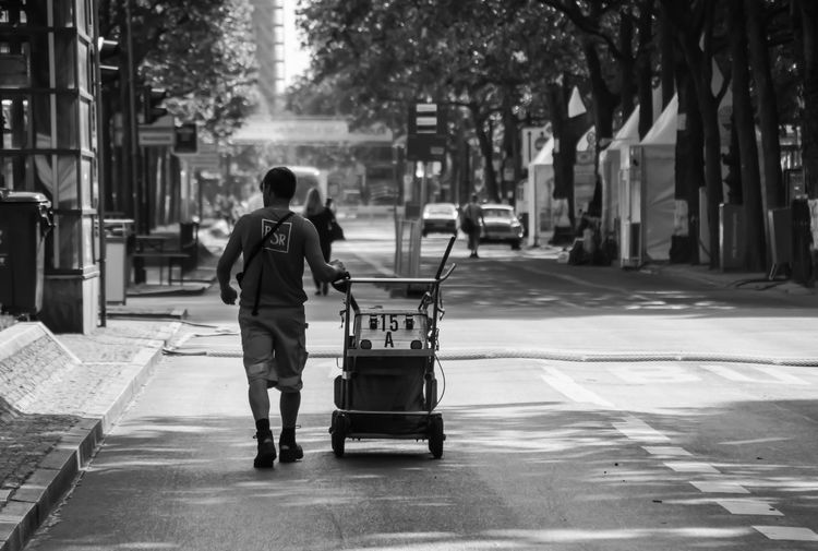 Rear View Of Man Pushing Cart On Street In City