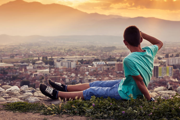 Boy sitting on cliff against city during sunset