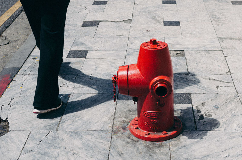 Low section of person walking by fire hydrant on footpath