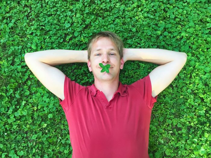 Portrait of man lying on plants with leaves in mouth