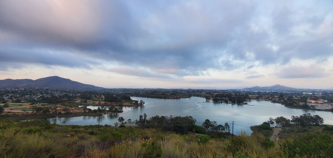 Panoramic view of lake by city against sky