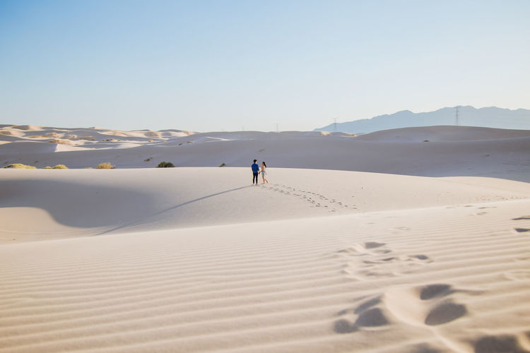 Mid distance view of couple walking on sand at desert against sky