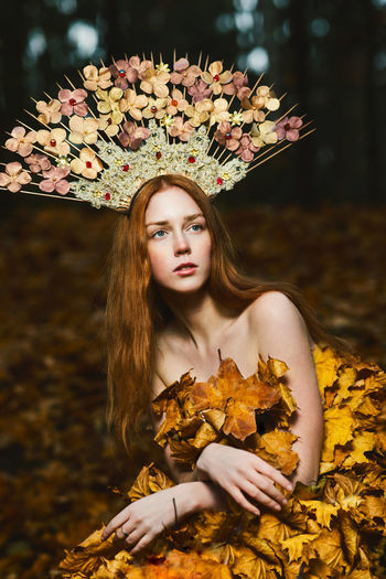 Portrait of beautiful young woman standing with leaves