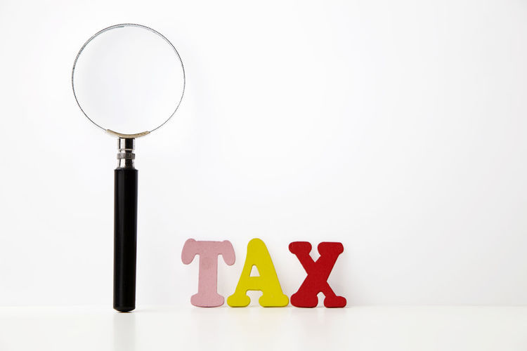 magnifying glass and word tax Alphabet Budget Enlarge Government Research Word Close-up Copy Space Focus Group Of Objects Income Indoors  Magnifier Magnifying Glass Multi Colored No People Saving Searching Side By Side Simplicity Still Life Studio Shot Tax Western Script White Background