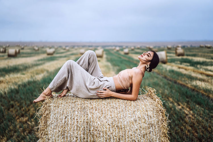 Woman relaxing on field against sky