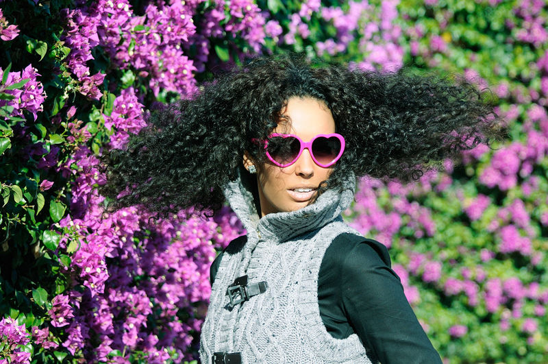 Young woman wearing sunglasses with tousled hair against bougainvillea