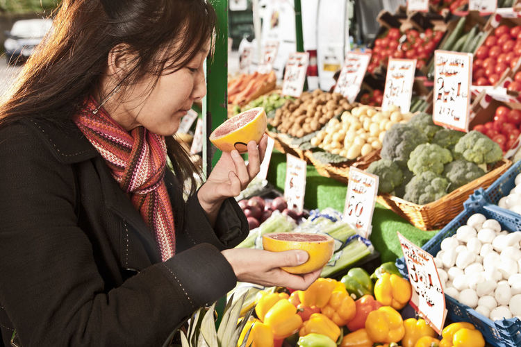 Midsection of woman holding food at market stall