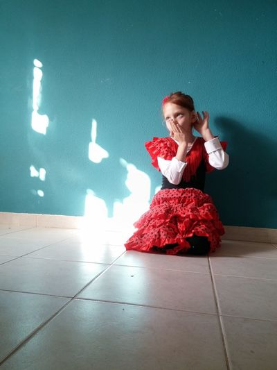 Girl in flamenco dance costume crouching on floor at home