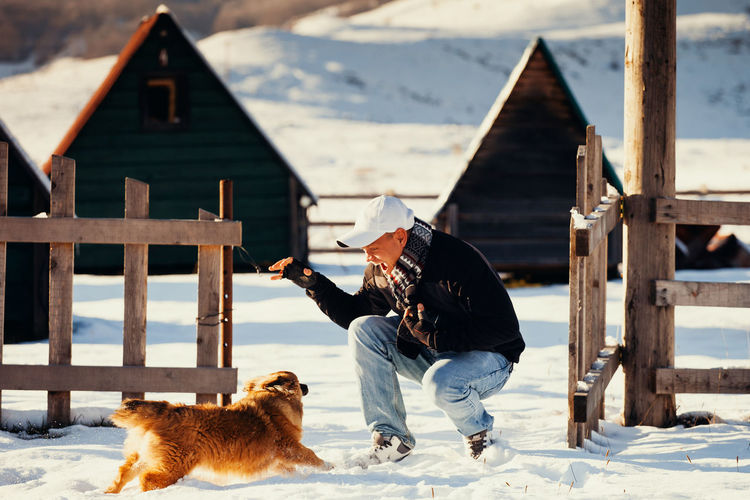 man plays with dog in winter. Joy and happiness EyeEm Best Shots Happiness Joyful Nature Snow ❄ Winter Casual Clothing Cold Days Cold Temperature Day Dog Domestic Animals Joy Leisure Activity Lifestyles Mammal Nature One Animal One Person Outdoors Pets Real People Snow Warm Clothing