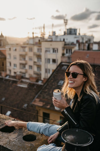 Happy woman in sunglasses having drink while sitting on retaining wall in city