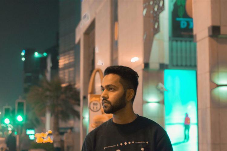 Young man in illuminated city at night