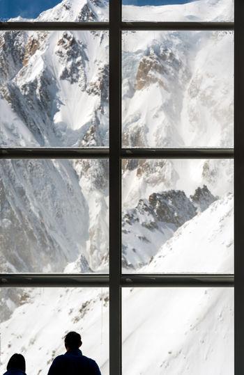 Snow covered mountains seen through window