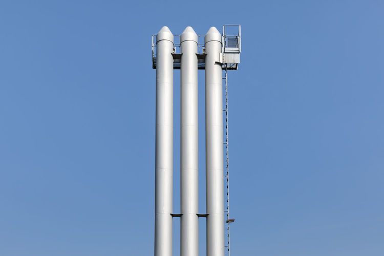 Low angle view of storage tanks against clear blue sky