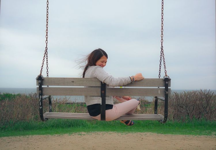 Side view of smiling mid adult woman sitting on swing at beach against cloudy sky