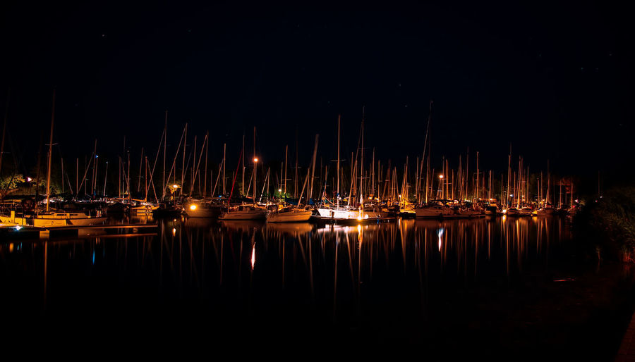 Reflection of boats in water at night
