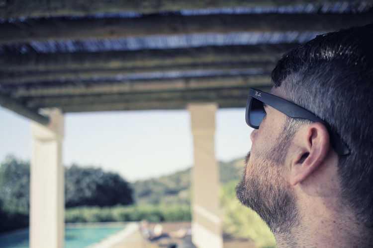 Man with sunglasses looking over view of swimming pool Sales Page Architecture Beard Built Structure Close-up Day Dof Focus On Foreground Headshot Landing Page Leisure Activity One Person Opt-in Box Outdoors People Real People Sunglasses Young Adult