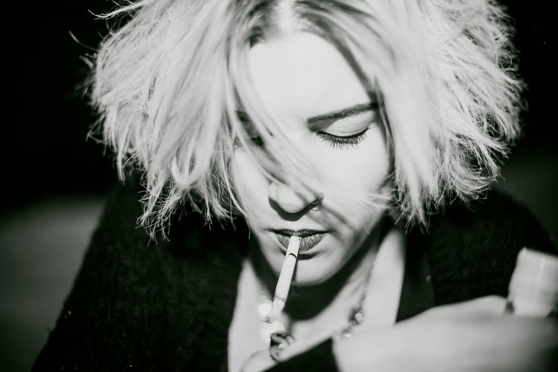 Close-Up Of Young Woman Lighting Cigarette