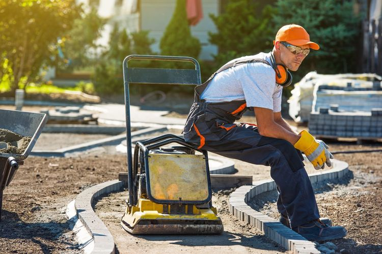 Brick Paver Worker Resting on His Soil Plate Compactor While at Work. Brick Pavers Casual Clothing Construction Industry Construction Site Day Full Length Hardhat  Hat Headwear Helmet Men Mode Of Transportation Occupation One Person Outdoors Paving Stone Real People Sitting Sunlight Transportation Working
