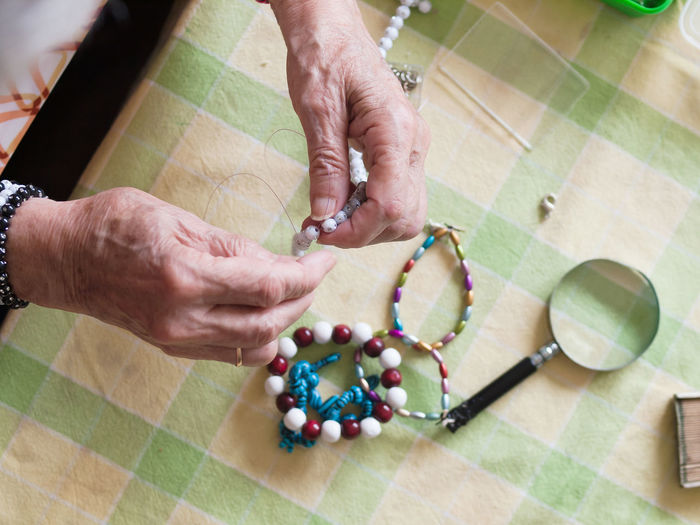 High angle view of woman making bracelet on table