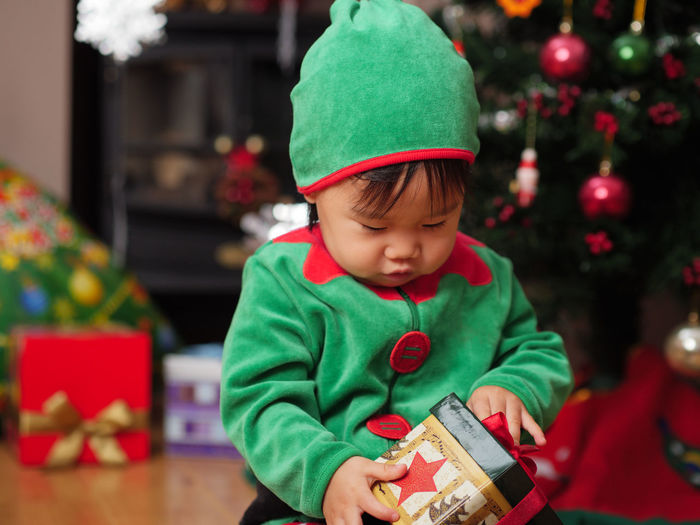 Close-up of baby girl with christmas gift at home
