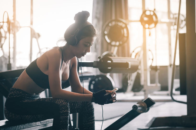 Woman Listening To Music On Headphones While Sitting In Gym