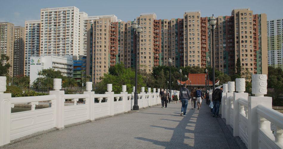 People on road by buildings against sky in city