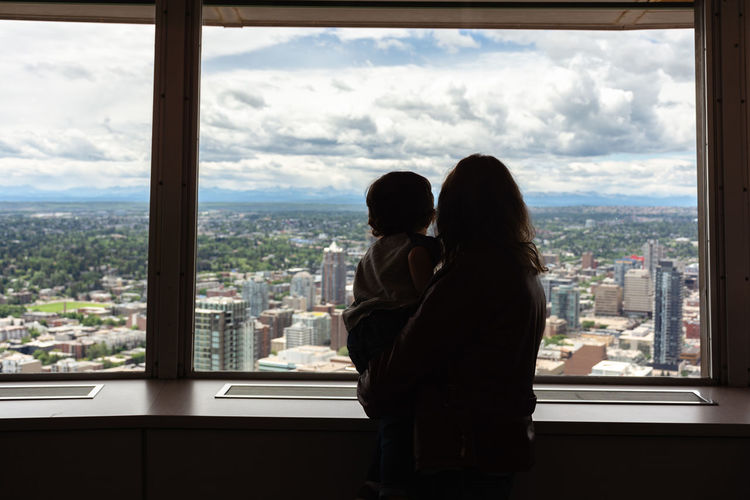 Rear View Of Mother And Son Looking Through Window