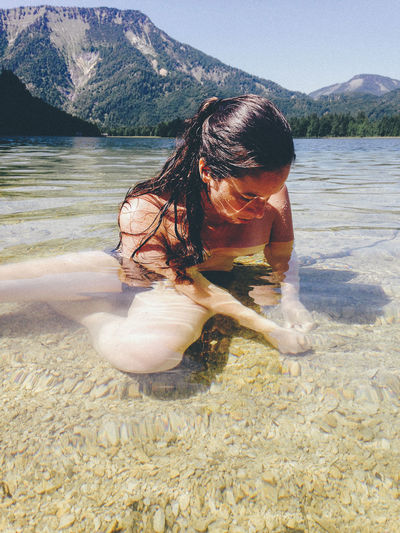 Young woman in water at mountain