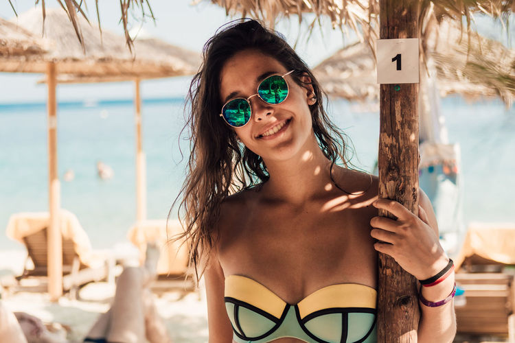 Beach Beautiful Woman Bikini Day Focus On Foreground Front View Happiness Leisure Activity Lifestyles Long Hair Looking At Camera One Person Outdoors Portrait Protection Real People Sea Smiling Summer Sunglasses Sunlight Vacations Water Young Adult Young Women