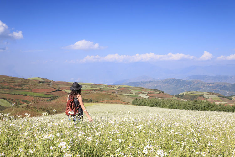 An unrecognizable girl enjoying DongChuan red land panorama, one of the landmarks in Yunnan Province, China Agriculture ASIA Autumn Beauty In Nature China Day Dongchuan Field Idyllic Kunming Landscape Leisure Activity Lifestyles Mountain Mountain Range Rear View Red Land Remote Scenics Sky Standing Terraces Tranquil Scene Tranquility Yunnan