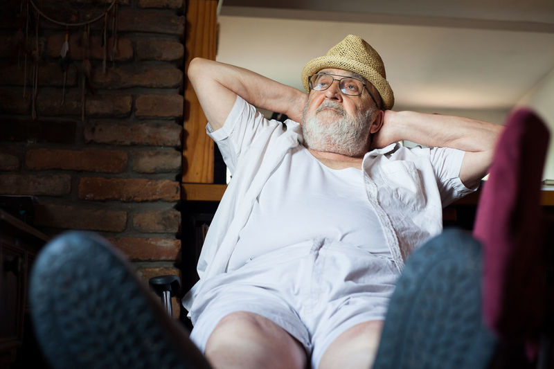 Low angle view of senior man relaxing at home