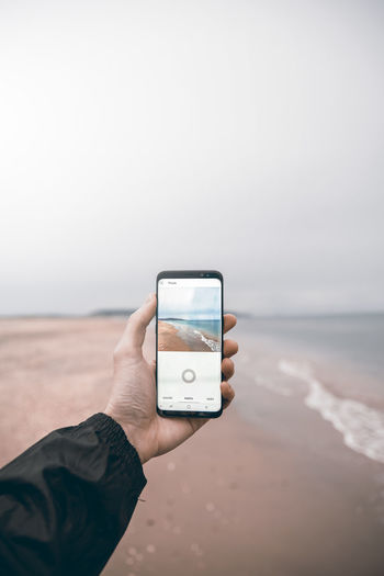 Man photographing with mobile phone at beach against sky