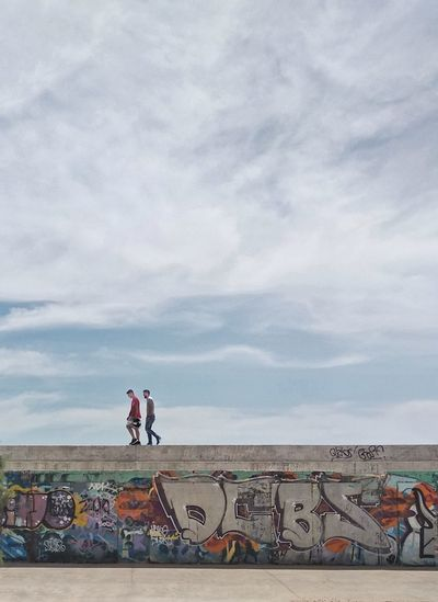People standing by graffiti on wall against sky