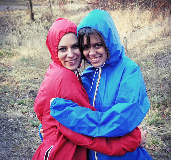 Two happy girls on a stormy day Smiling Portrait Bonding Emotion Happiness Women Lifestyles Leisure Activity People Clothing Positive Emotion Sister Looking At Camera Girl Raincoat Rain Jacket Weather Fun Nature Spring Autumn Cold Temperature Cheerful Happy Storm