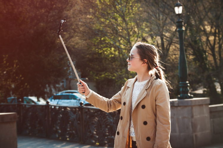 Girl Holding Monopod While Taking Selfie Through Smart Phone During Winter