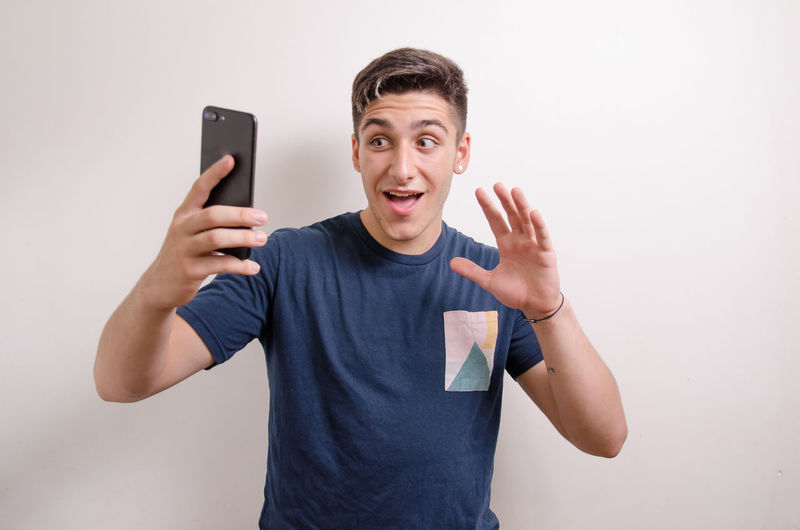 Portrait of young man using mobile phone against white background