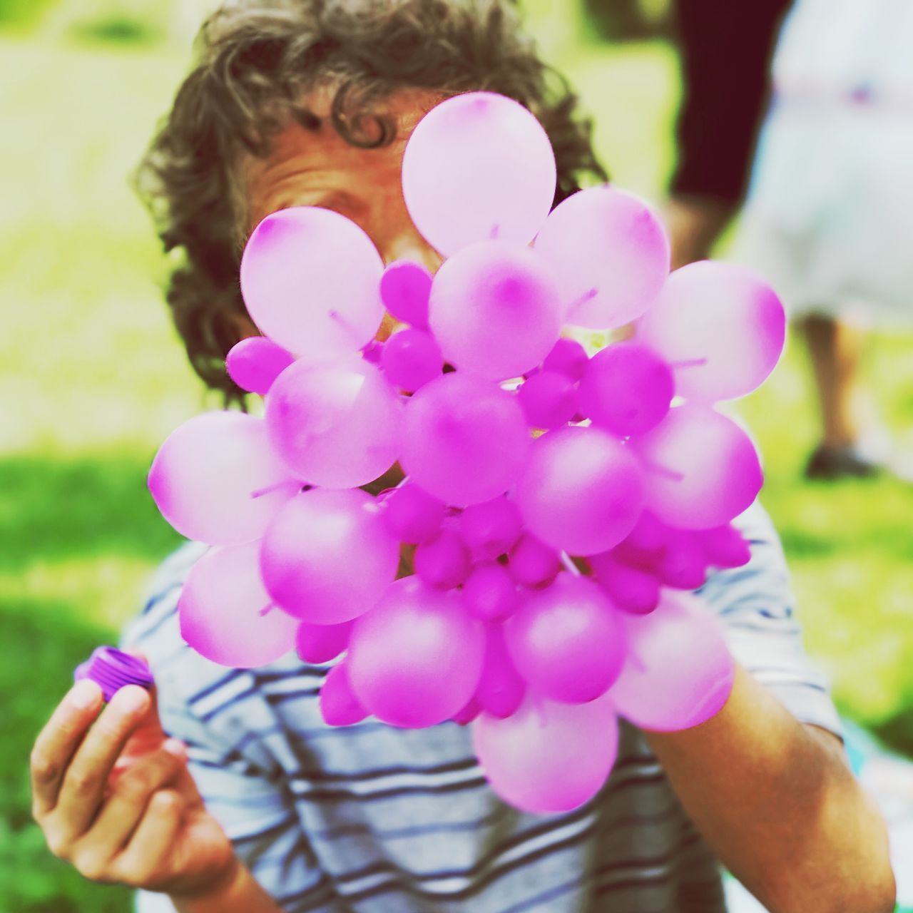 real people, one person, holding, human hand, outdoors, focus on foreground, day, pink color, human body part, childhood, leisure activity, lifestyles, park - man made space, flower, nature, close-up, beauty in nature, fragility, women, balloon, freshness, grass, flower head, people