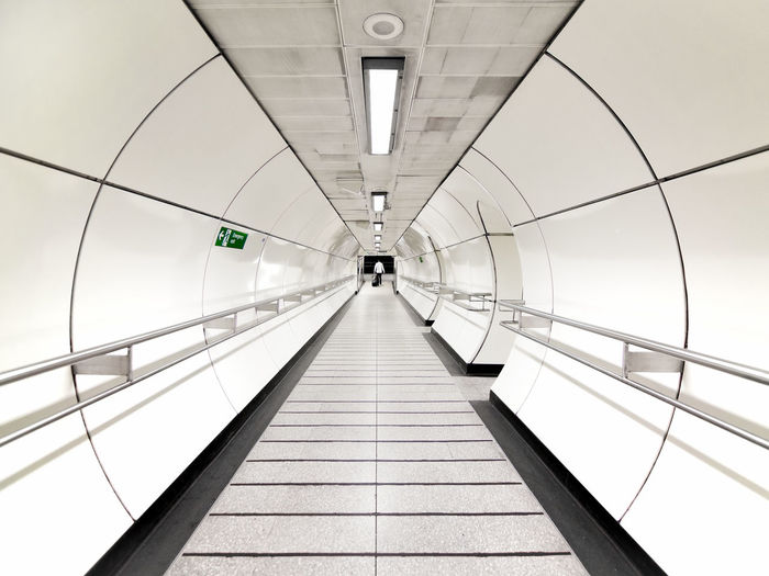 A man walking down a tunnel into the London Underground system Light London Lonely Man Transport For London Transportation Trip Underground Aseptic Commute Handrail  Lone Subway Train Tunnel White