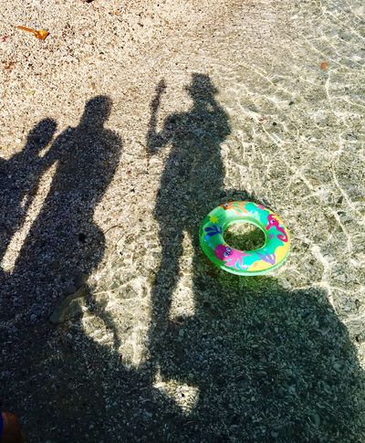 Shadows of family over ocean water and colorful float toy Shadow Real People Sunlight High Angle View Focus On Shadow Leisure Activity Outdoors Men Day Low Section Multi Colored Lifestyles Women Sand One Person Human Body Part The City Light Sommergefühle Neon Life Connected By Travel