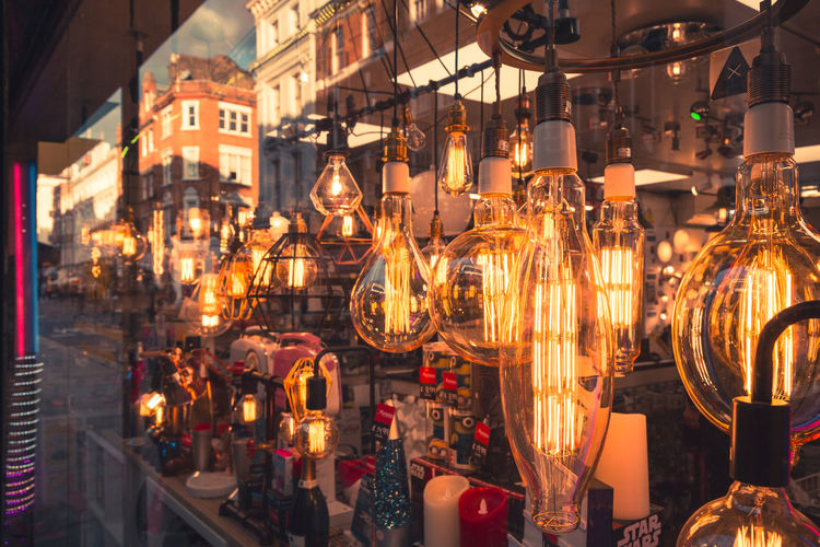 Vintage style filament bulbs hanging in a shop window display in London. Architecture Bazaar Canon Canon 5d Mark Lll City Filament Filament Bulb Filament Light Hanging Hanging Light Illuminated Large Group Of Objects Lightbulb Lighting Equipment London Neon Night No People Orange Color Outdoors Reflection Retail  Shopfront Store Vintage Lights