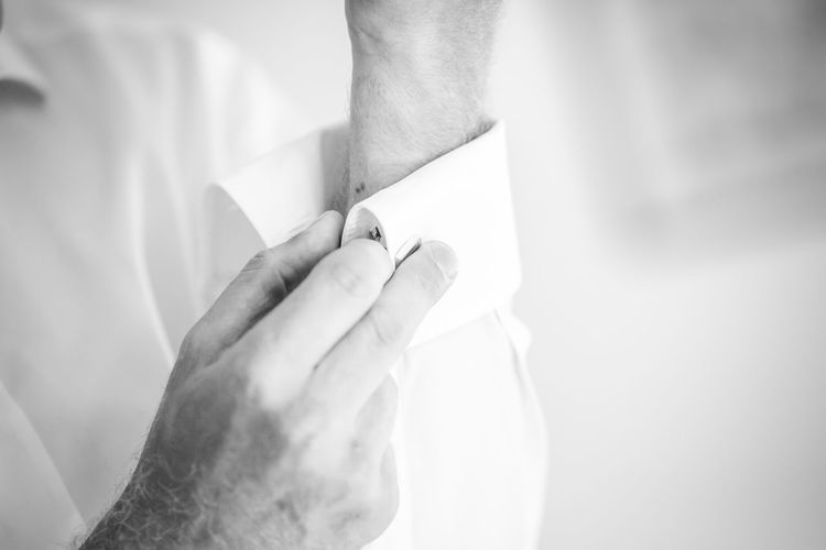 Cropped image of man buttoning sleeve