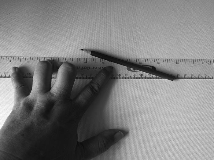 Cropped hand holding ruler and pencil on table